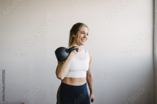 Smiling female athlete carrying kettlebell while standing by wall in gym