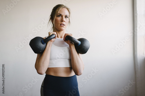 Portrait of female athlete carrying kettlebells while standing by wall in gym