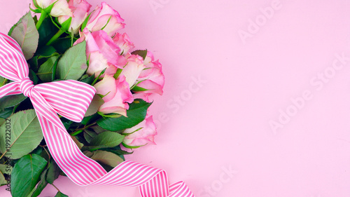 Happy Mother's Day background of pink roses with copy space on pink wood table.