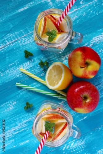 letni-napoj-z-pomarancza-jablkiem-cytryna-i-lodem-na-drewnianym-stole-niebieskie-tlo-slomki-widok-z-gory