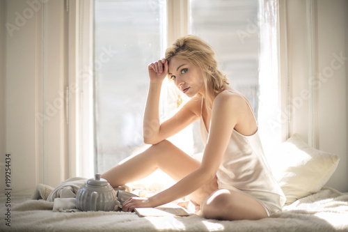 Fotografie, Obraz  Beautiful attractive girl chilling in her bed next to the window
