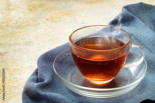 Staande foto Thee freshly brewed black tea in a glass cup, steaming hot drink on a blue napkin, copy space