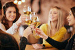 canvas print picture - Girlfriends drinking wine and chatting while sitting in the bar.