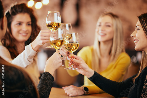 Girlfriends drinking wine and chatting while sitting in the bar. Fototapet