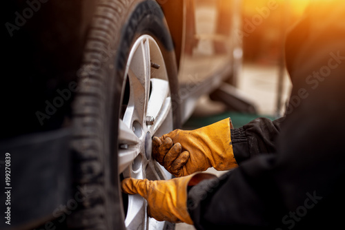 Fototapeta An experienced mechanic with orange gloves is putting screws on a placed wheel on a car. obraz