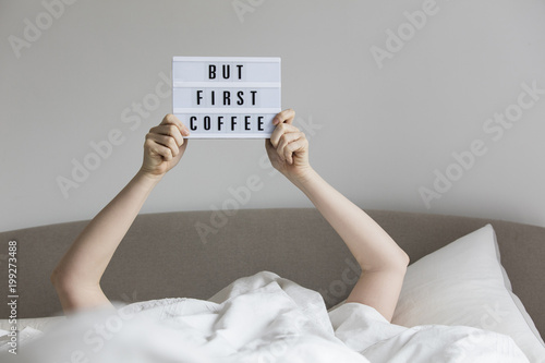 Female in bed under the sheets holding up a but first coffee sign Canvas Print