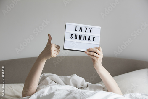Obraz Female in bed under the sheets holding up a lazy sunday sign - fototapety do salonu