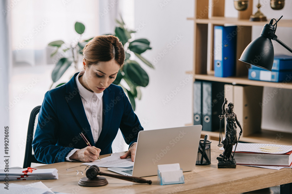 Fototapeta female lawyer in suit at workplace with laptop, gavel and femida in office