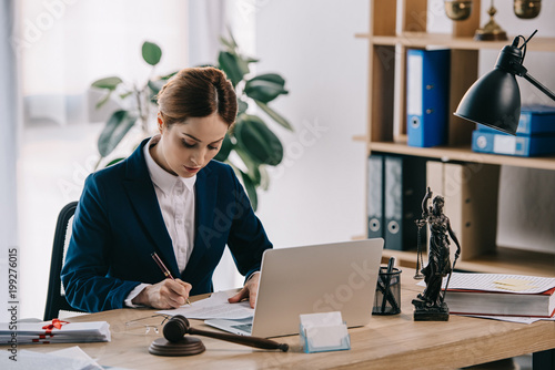 Fototapeta female lawyer in suit at workplace with laptop, gavel and femida in office obraz