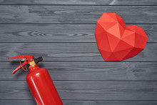 Hot Love, Burning Love Concept. Top View Of Red Polygonal Heart Shape And Fire Extinguisher On Wooden Planks