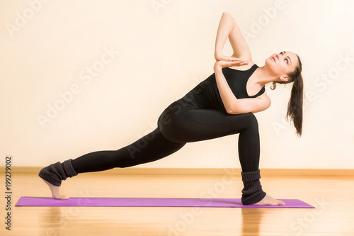 Fotografie, Obraz  Young woman is practicing anjaneyasana yoga pose at gym background