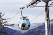 Ski lift cable booth or car, Ropeway and cableway transport sistem for skiers with fog on valley background