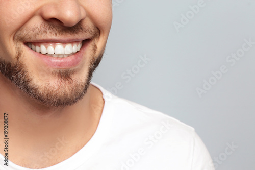 Young man with beautiful smile on grey background Fototapet
