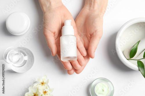 Fotografie, Obraz  Woman holding bottle of cream over table with cosmetic products