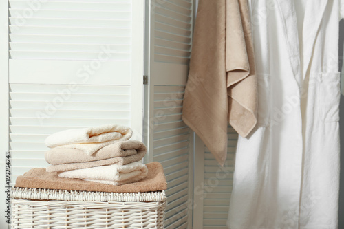 Stack Of Clean Towels On Laundry Basket In Bathroom