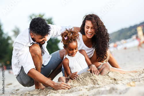 obraz PCV Young mixed race family sitting and relaxing at the beach on beautiful summer day.Playing in the sand.