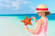 Adorable girl with starfish on the beach. Closeup starfish in the hands of a little girl