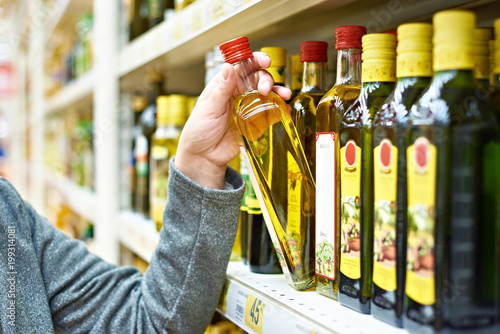 Bottle of olive oil in hand buyer at grocery