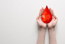 Two Hands Holding Red Polygonal Blood Drop, Blood Donation Concept. Poster With Place For Text For Clinic, Hospital.