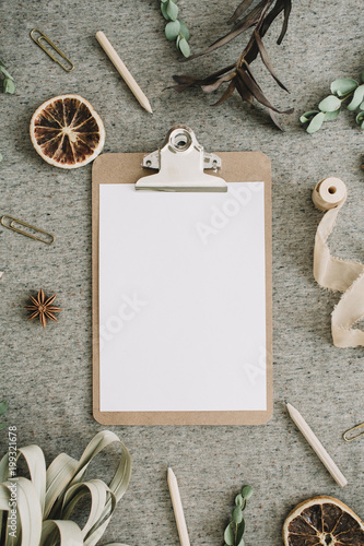 Clipboard with blank paper mock up in frame of eucalyptus branches ...