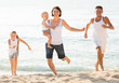 parents with two kids jogging on beach .
