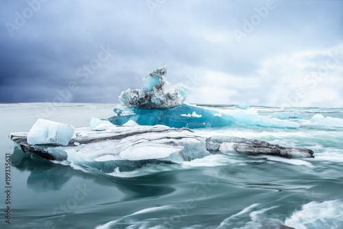 Tuinposter Ijsbeer bizarre große blaue Eisformation auf dem Wasser