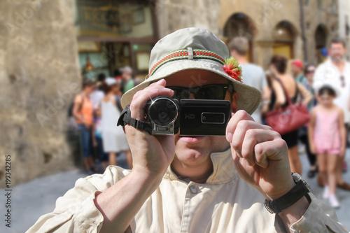 Fotografie, Obraz  Tourist mit Videokamera und Sonnenhut