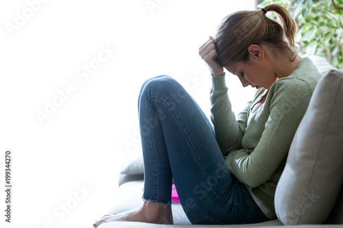 Foto Unglückliche einsame deprimierte junge Frau, die zu Hause auf Sofa sitzt