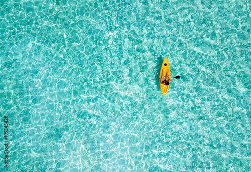 Frau im Kajak paddelt über das türkise Wasser der Malediven