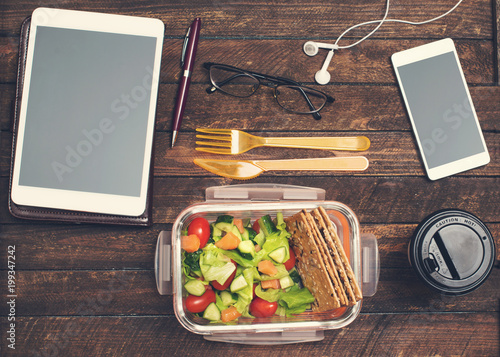 Papiers peints Assortiment Healthy business lunch at workplace. Salad, salmon, avocado lunch box on working desk with tablet, smartphone, glasses and headphones.
