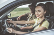 canvas print picture - Our best adventure. Portrait of charming young woman is sitting in car with her boyfriend and smiling. She is driving and looking at camera happily. Selective focus