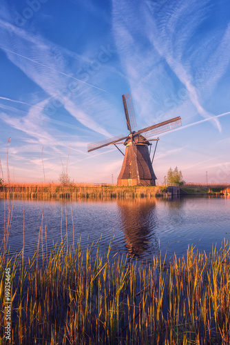 Scenic sunset landscape with windmill, blue sky and reflection in the water. Traditional dutch countryside, famous village of mills Kinderdijk, Netherlands (Holland), vertical image