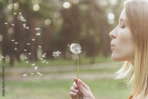 Cuadros en Lienzo tranquil woman standing in park and blowing on dandelion