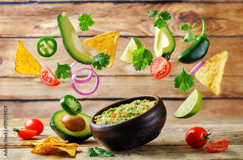 Fotografie, Obraz  Guacamole with flying corn chips and ingredients to prepare it