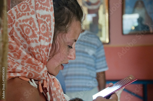 Young parent at the church wearing a christening gown. Fototapeta