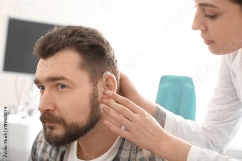 Valokuva  Otolaryngologist putting hearing aid in man's ear in hospital