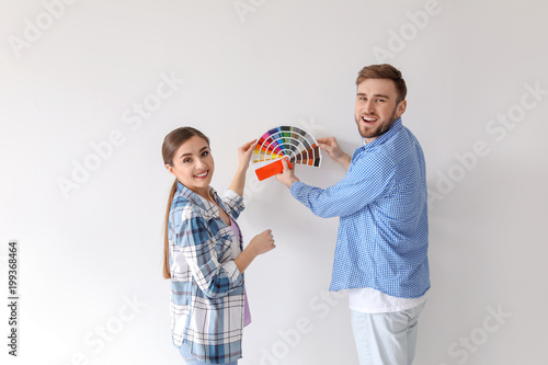 Young couple with color palette on white background