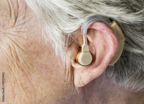 Elderly woman wearing a hearing aid Canvas Print