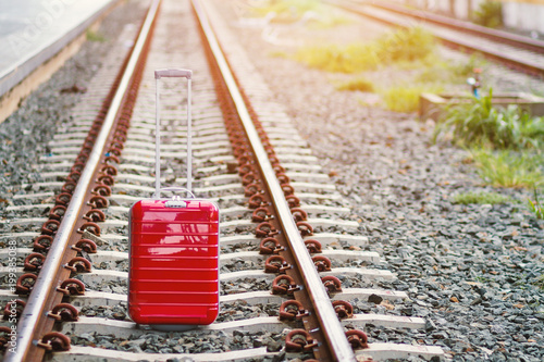 Poster Voies ferrées Red suitcase in the middle of the railroad tracks.