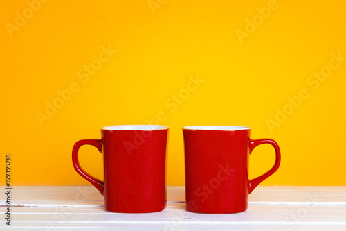 Two red coffee mugs on a yellow background with copt space.