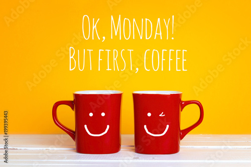 Two red coffee mugs with a smiling faces on a yellow background with the phrase Ok, mondey, but firrst coffee.