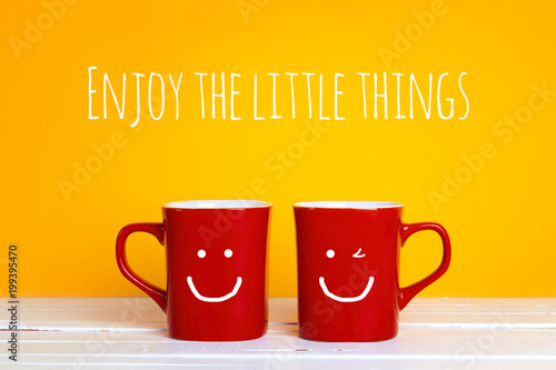 Two red coffee mugs with a smiling faces on a yellow background with the phrase Enjoy the little things.