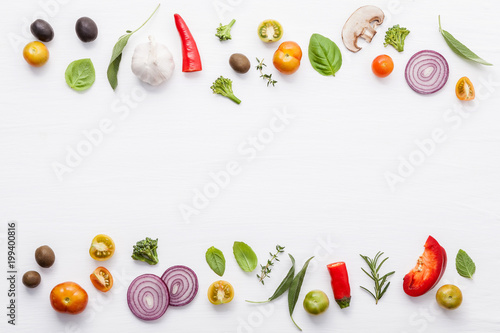 Various fresh vegetables and herbs on white background.Ingredients for cooking concept sweet basil ,tomato ,garlic ,pepper and onion with flat lay..