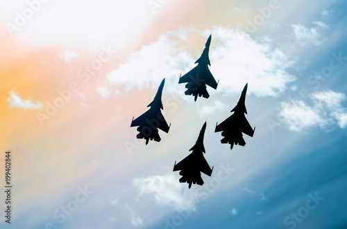 Group of four aircraft fighter jet airplane sun glow toned sky. Canvas Print