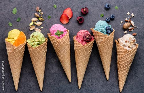 Fotografie, Obraz  Various of ice cream flavor in cones blueberry ,strawberry ,pistachio ,almond ,orange and cherry setup on dark stone background