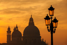 Old Traditional Venice Street Lamps At Sunset With Salute Basilica Old Domes In A Romantic Atmosphere