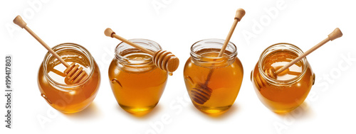 Honey pot with wooden dipper set isolated on white