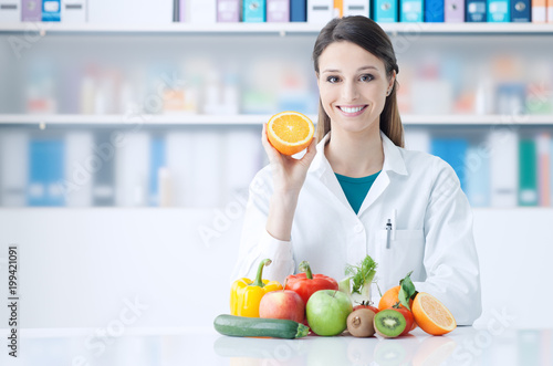 Nutritionist holding a sliced orange Canvas Print