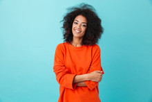 Colorful Portrait Of Amazing Woman In Red Shirt With Afro Hairstyle Looking On Camera With Smile, Isolated Over Blue Background