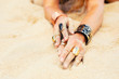 Woman's hands with expressive jewelry in sand